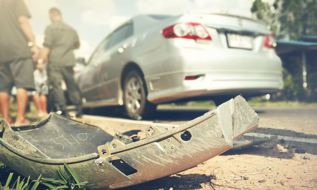 The aftermath of a car crash. Bumper on the floor with people swapping information in the background. Photo: GITTI.NUNCHO/Shutterstock.com