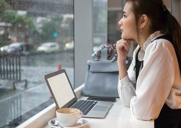woman at rainy window with laptop