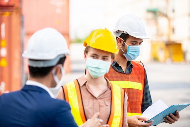two workers and manager at warehouse wearing masks