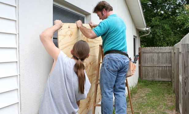 Homeowner boarding up windows.