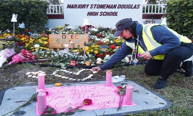 School crossing guard Wendy Behrend lights a candle at a memorial outside Marjory Stoneman Douglas High School during the one-year anniversary of the school shooting, Thursday, Feb. 14, 2019, in Parkland, Fla. (AP Photo/Wilfredo Lee)