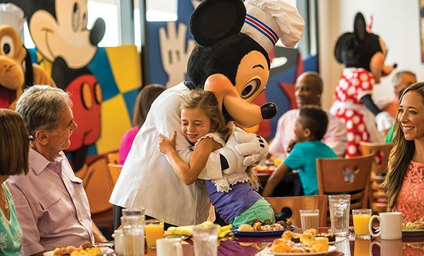 Mickey Mouse hugs a guest.