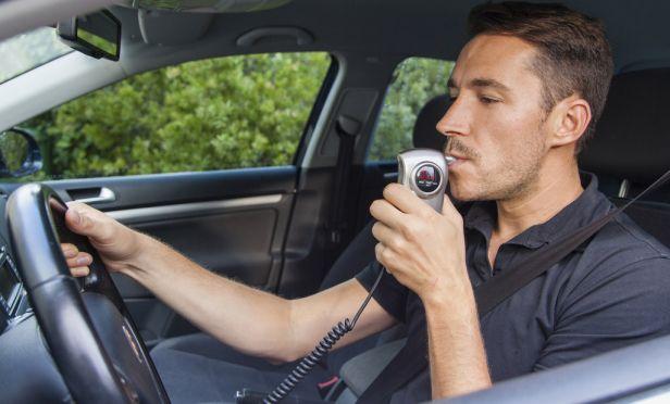 Male driver using breathalyzer