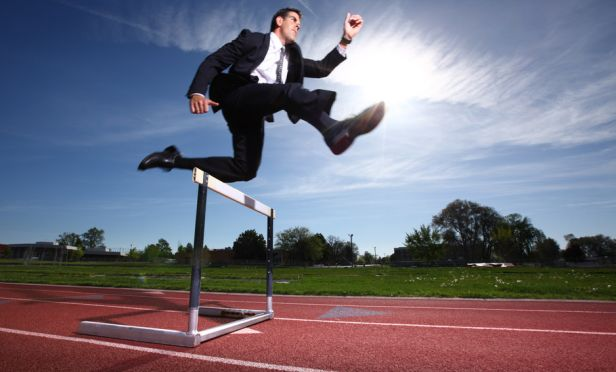 businessman jumping a track hurdle