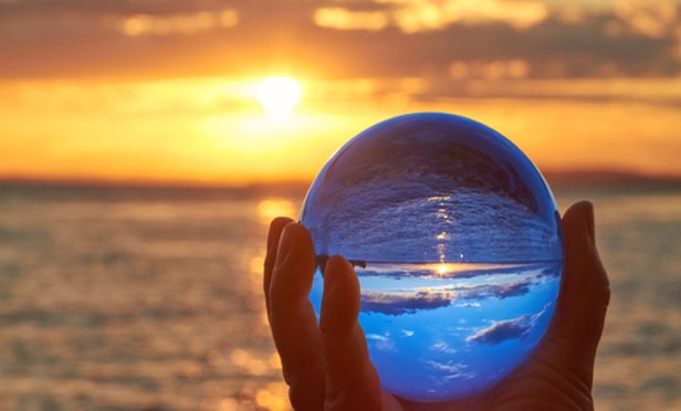 Hand holding crystal ball up against horizon at sunset
