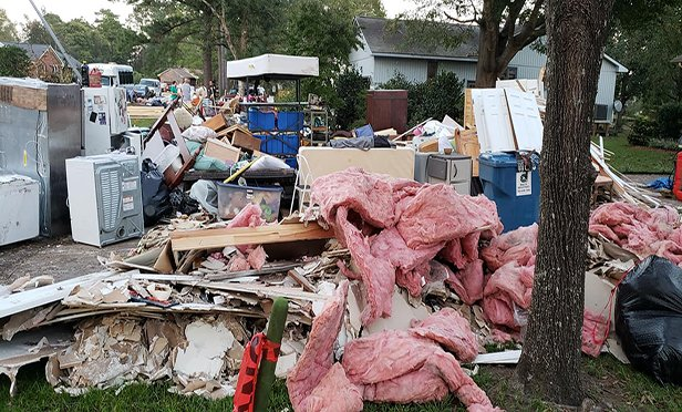 Damaged personal property and debris from a gutted dwelling sit outside a house in River Bend, N.C. The home and neighborhood were devastated by Hurricane Florence. (Contributed photo: L. R. LaMotte)