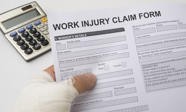 injured worker holding workers' comp claim form