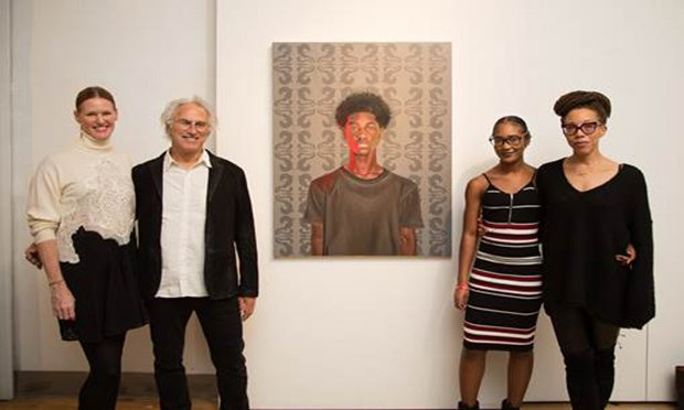 Four people standing with a painting