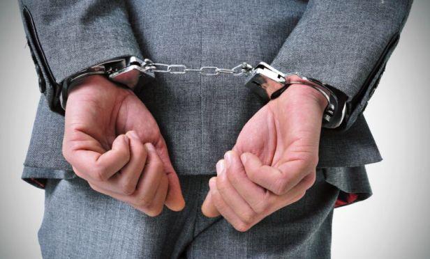 Insurance agent in handcuffs