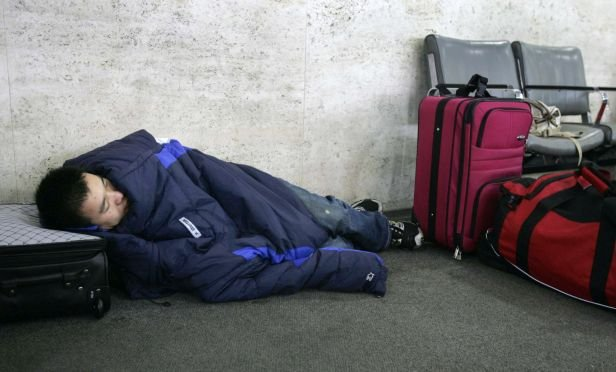 Stranded traveler sleeping in airport