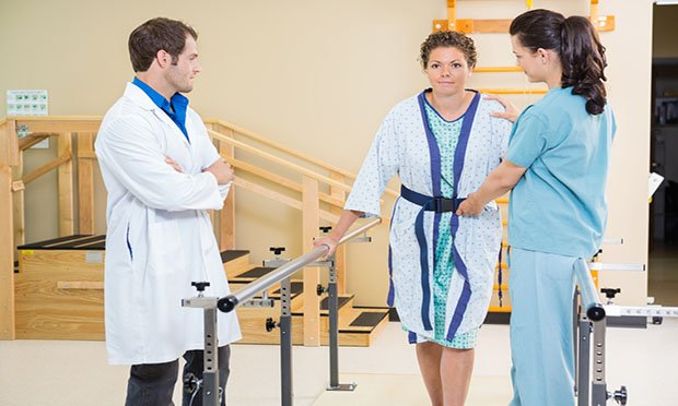 Adult woman patient doing physical rehab with therapist and doctor