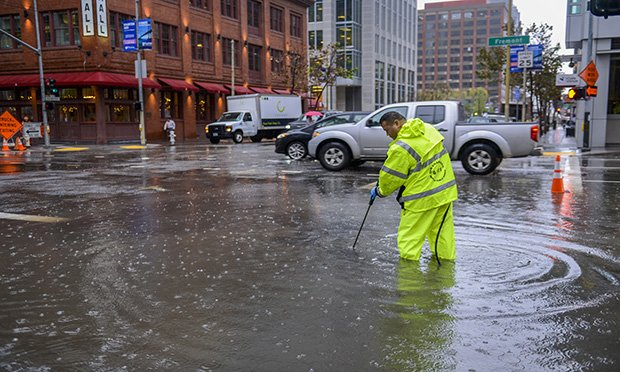 Public works employee cleaning clogged storm drain in San Francisco.