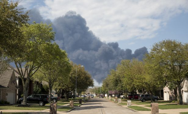 A plume of smoke rises above homes