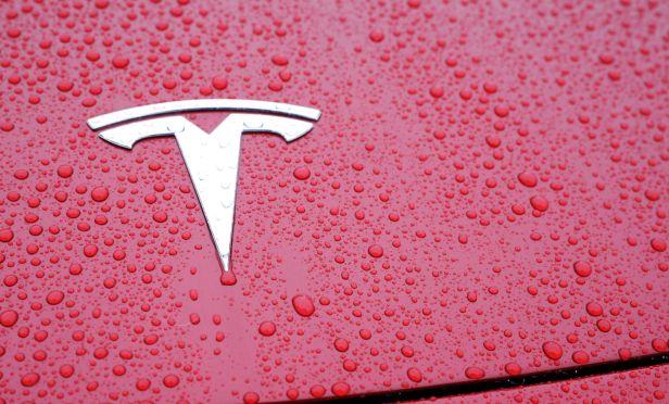 Tesla emblem on a red car.