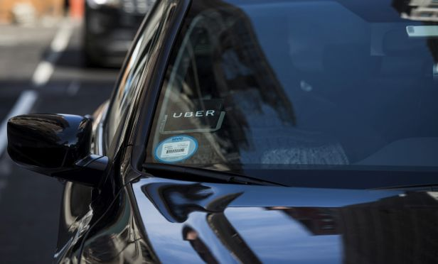The Uber logo is seen on the windshield of a vehicle