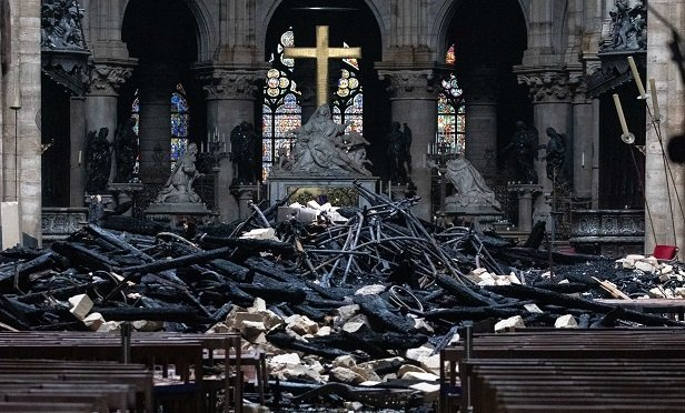 Fallen debris from the burnt out roof structure sits near the high altar inside Notre Dame Cathedral in Paris, France, on Tuesday, April 16, 2019. Authorities declared Tuesday morning that the blaze had been contained as firefighters hosed the south side of the transept to cool down the building, and a district around the cathedral was sealed as military and police patrolled the area. (Photographer: Christophe Morin/Bloomberg)