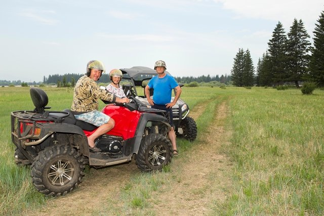 Three people with helmets in rural area riding ATVs