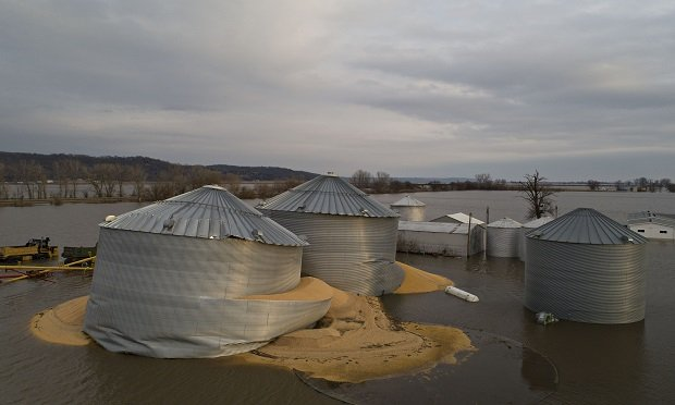 Floodwaters surround corn sitting under a collapsed grain bins in this aerial photograph over Pacific Junction, Iowa, U.S., on Saturday, March 23, 2019. The deluge that devastated so much of the Midwest over the last week could be a preview for one of the worst years for flooding in the U.S., according to federal weather officials. (Photographer: Daniel Acker/Bloomberg)