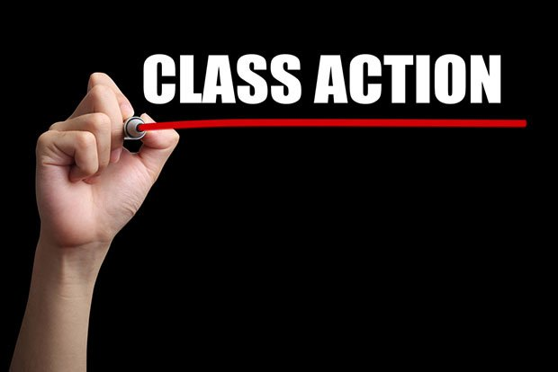 Hand writing class action on blackboard red underline