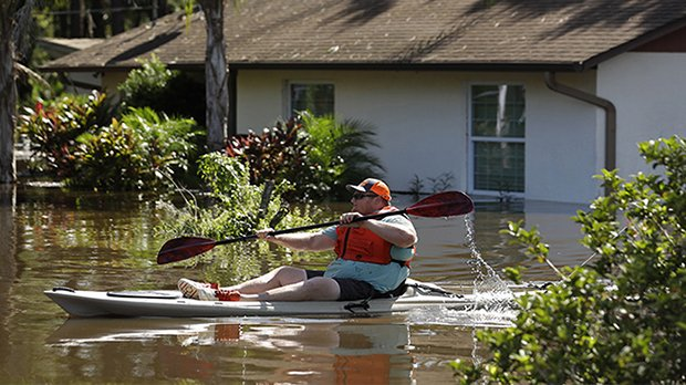 Man-paddling-kayak-on-flooded-street