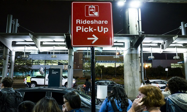 Mobility ecosystems present an opportunity for insurers to step up and catch up when it comes to technology. Here, customers wait for their rides beneath a Rideshare pick-up sign at Chicago's Midway airport. (Diego M. Radzinschi/ALM Media)