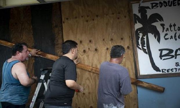 Men board up a shop's windows ahead of the arrival of Tropical Storm Dorian in Boqueron, Puerto Rico, Tuesday, Aug. 27, 2019. (AP Photo/Ramon Espinosa)