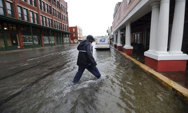 A postman walks through streets flooded by Tropical Depression Imelda as he deliver mail on Wednesday, Sept. 18, 2019, in Galveston, Texas. (AP Photo/David J. Phillip)