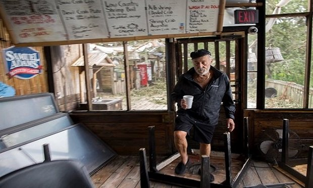 A restaurant owner surveys the damage to his business after a hurricane. (Photo: AP)