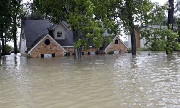 A home is surrounded by floodwaters from Tropical Storm Harvey on Monday, Aug. 28, 2017, in Spring, Texas. Homeowners suffering from Harvey flood damage are more likely to be on the hook for losses than victims of prior storms, a potentially crushing blow to personal finances and neighborhoods along the Gulf Coast. Experts say far too few homeowners have flood insurance, just two of ten living in Harvey's path of destruction. (AP Photo/David J. Phillip)