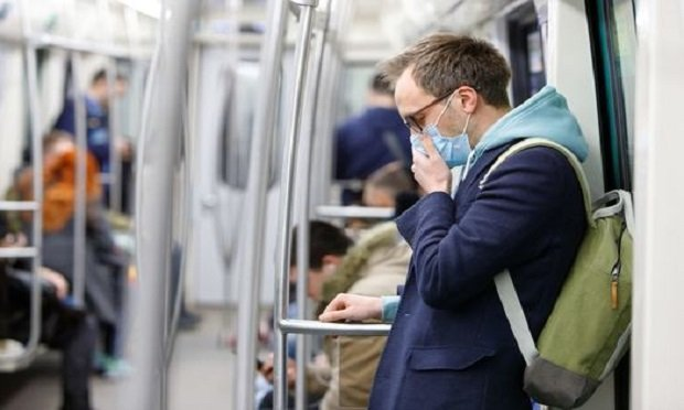 A man wearing a protective mask while commuting on a train. (Photo: Shutterstock)