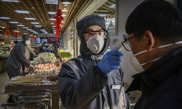 A Chinese worker checks the temperature of a customer as he wears a protective suit and mask at a supermarket on February 11, 2020 in Beijing, China. The number of cases of a deadly new coronavirus rose to more than 42000 in mainland China Tuesday, days after the World Health Organization (WHO) declared the outbreak a global public health emergency. China continued to lock down the city of Wuhan in an effort to contain the spread of the pneumonia-like disease which medicals experts have confirmed can be passed from human to human. In an unprecedented move, Chinese authorities have put travel restrictions on the city which is the epicentre of the virus and municipalities in other parts of the country affecting tens of millions of people. The number of those who have died from the virus in China climbed to over 1000 on Tuesday, mostly in Hubei province, and cases have been reported in other countries including the United States, Canada, Australia, Japan, South Korea, India, the United Kingdom, Germany, France and several others. The World Health Organization has warned all governments to be on alert and screening has been stepped up at airports around the world. Some countries, including the United States, have put restrictions on Chinese travellers entering and advised their citizens against travel to China. (Photo by Kevin Frayer/Getty Images)