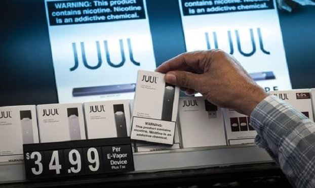A salesman reaches for a of Juul Labs Inc., device kit for a customer at Discount Cigarettes and Cigars store in San Francisco, California, U.S., on Wednesday, June 26, 2019. The city voted Tuesday to ban sales of e-cigarettes, making it illegal to sell nicotine vaporizer products in stores or for online retailers to ship the goods to San Francisco addresses. Photographer: David Paul Morris/Bloomberg