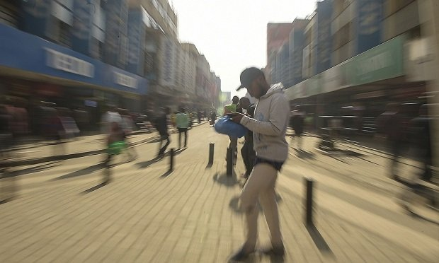 A man using his mobile phone walks along a street in down town Nairobi on July 24, 2019. (Photo by SIMON MAINA / AFP) (Photo credit should read SIMON MAINA/AFP via Getty Images)