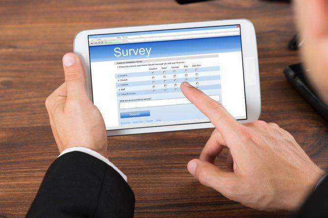 Man's-hands-tablet-taking-survey
