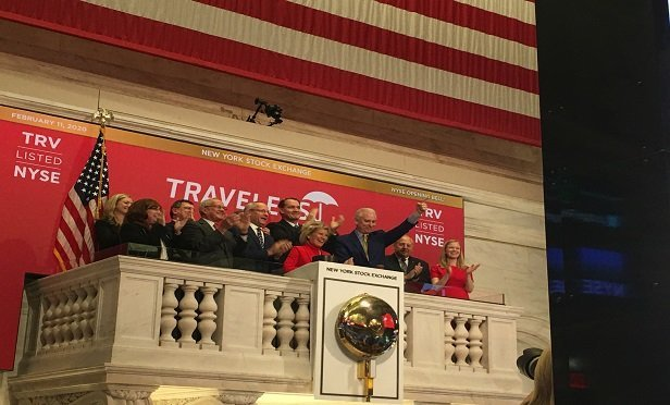 Joan Woodward, center, stands with other executives from Travelers as she rings the opening bell at the New York Stock Exchange. (Photo: Denny Jacob)