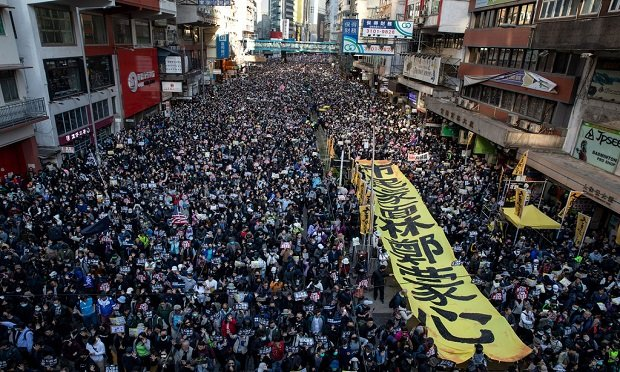 Political unrest can result inproperty damage, business interruption (BI) and a loss of income for many businesses. Here, demonstrators march through Hong Kong to mark Human Rights Day and press for greater democracy in the city. (Kyle Lam/Bloomberg)