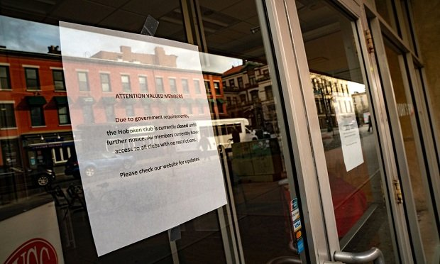 A sign notifying facility closure hangs on a window of a New York Sport Club (NYSC) location in Hoboken, New Jersey, U.S., on Monday, March 16, 2020. (David 'Dee' Delgado/Bloomberg)