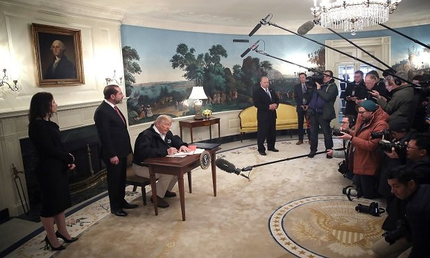 Donald Trump signs a coronavirus funding bill he signed at the White House on March 6, 2020.
