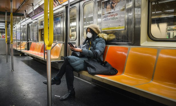 A commuter wears a face mask as she sits alone on the subway during the coronavirus pandemic in New York, Tuesday, March 17, 2020. (Photo: Ryland West/ALM)