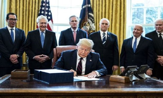 U.S. President Donald Trump signs the H.R. 748, Coronavirus Aid, Relief, and Economic Security (CARES) Act, in the Oval Office of the White House in Washington, D.C., U.S., on Friday, March 27, 2020. Trump signed the largest stimulus package in U.S. history today, a $2 trillion bill intended to rescue the coronavirus-battered economy after the House approved it earlier. (Photo: Erin Schaff/The New York Times/Bloomberg)