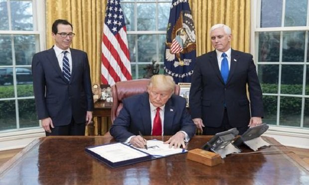 President Donald J. Trump, joined by Vice President Mike Pence and Treasury Secretary Steven Mnuchin, signs H.R. 6201, the Families First Coronavirus Response Act on Wednesday, March 18, 2020, in the Oval Office of the White House. (Official White House Photo by Shealah Craighead)