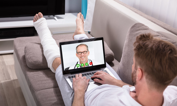 Man-on-couch-bandaged-leg-video-doctor visit