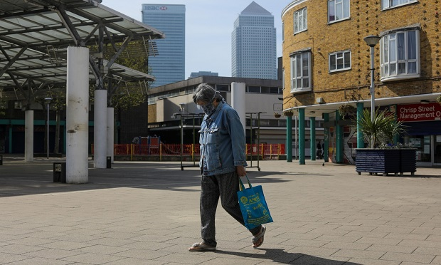 A pedestrian wearing a protective face mask passes shuttered shops at Chrisp Street Market in London, U.K. (Photo: Simon Dawson/Bloomberg)