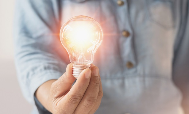 Man holding a lit light bulb.