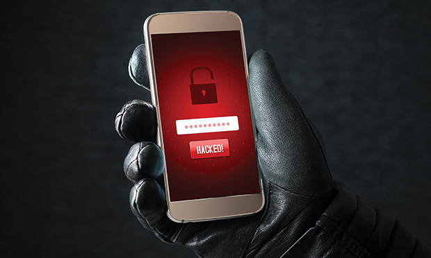 Gloved hand holding a hacked cell phone.