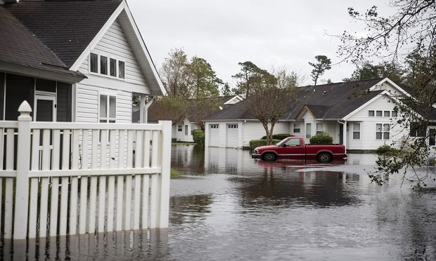 Flood insurance suffers from some ill-informed, preconceived notions. As a result, 57 million homes in the United States have significant flood exposure. Here, A truck sits partially submerged in a flooded North Carolina neighborhood after Hurricane Florence. (Alex Wroblewski/Bloomberg)
