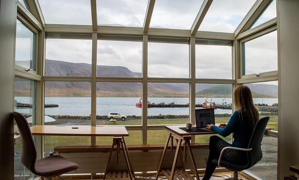 Woman working remotely from her sunroom overlooking the water.
