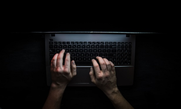 Hacker's hands on a computer keyboard