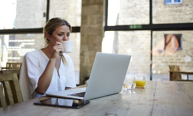 Young woman drinking coffee in front of her computer at home.
