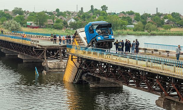 Collapsed bridge with a truck stuck in the middle.